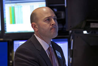 Specialist Jay Woods works Jan. 29 at his post on the floor of the New York Stock Exchange. AP Photo Richard Drew - AP