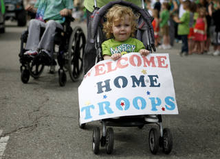 Jericho Biffel, 2, holds a sign welcoming troops home during the annual St. Patrick's Day Parade in downtown Oklahoma City, Saturday, March 17, 2012. Jericho's father, Jerry Biffel, is deployed with the 45th Infantry Brigade Combat Team and will be returning from Afghanistan. Photo by Bryan Terry, The Oklahoman