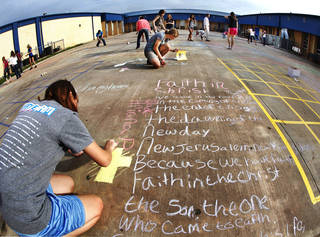 Ariana Polach, a freshman, creates an illustration beside her poem. Students in Dustin Johnson's freshman English classes at Choctaw High School observed National Poetry Month and Poem in Your Pocket Day by writing poems in chalk. Photos by Jim Beckel, The Oklahoman