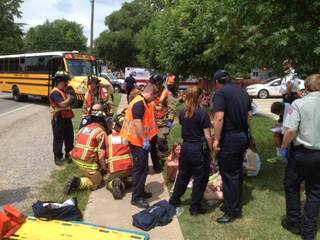 Police and paramedics help children who were injured Wednesday when the Cleveland County YMCA bus in which they were riding was involved in a wreck shortly after noon. PHOTO BY STEVE SISNEY, THE OKLAHOMAN