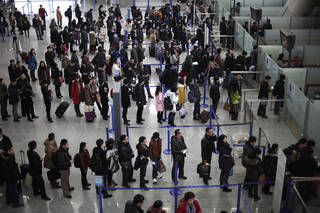 Passengers line up for a security check at Pudong International Airport in Shanghai, China. AP File Photo Eugene Hoshiko -