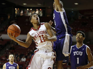 Oklahoma's Isaiah Cousins (11) puts up a shot beside TCU's Brandon Parrish (11) and Karviar Shepherd (1) during an NCAA college basketball game between the University of Oklahoma (OU) and Texas Christian University (TCU) at Lloyd Noble Center, Wednesday, Jan. 22, 2014. Oklahoma won 77-69. Photo by Bryan Terry, The Oklahoman