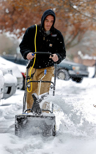 University of Oklahoma facilities employee Aaron Hanna clears the sidewalks near the dormitories on Friday in Norman. Photo by Steve Sisney, The Oklahoman STEVE SISNEY - THE OKLAHOMAN