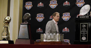FILE - In this Jan. 8, 2013, file photo, Alabama head coach Nick Saban walks past national championship trophies at a BCS National Championship college football news conference in Ft. Lauderdale, Fla. Alabama will begin this season the way it ended the last two — No. 1. Nick Saban and the two-time defending national champion Crimson Tide are top-ranked in The Associated Press preseason college football poll released Saturday, Aug. 17, 2013, as they try to become the first team to win three straight national titles. (AP Photo/Morry Gash, File) ORG XMIT: NY117