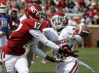 Oklahoma defender Brandon Young (38) breaks up a pass intended for wide receiver Trey Metoyer (17) during the annual Oklahoma spring intra-squad NCAA college football game in Norman, Okla., Saturday, April 13, 2013. (AP Photo/Sue Ogrocki)