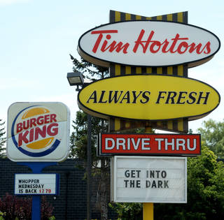 A Burger King sign and a Tim Hortons sign are shown Monday in Ottawa, Ontario. Burger King is in talks to buy Tim Hortons and may move its headquarters to Canada. AP Photo Sean Kilpatrick -
