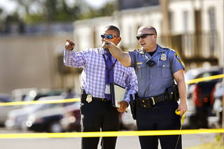 A patrol officer and a detective share information Tuesday afternoon at a shooting scene at Windsong Village Apartments near Interstate 240 and S Walker Avenue. Photo by Jim Beckel, The Oklahoman. Jim Beckel - THE OKLAHOMAN