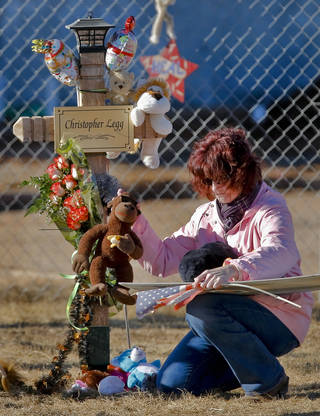 Tammy DeWitt takes a moment next to the cross of her nephew Christopher Legg to remove momentos after a balloon release to mark would have been Legg's tenth birthday outside the Plaza Towers Elementary School in Moore, Okla. on Thursday, Jan. 16, 2014. Christopher was killed along with six others when the May 20th tornado hit the school. Parents of those killed have been notified that the crosses will need to be removed for further rebuilding of the school. Photo by Chris Landsberger, The Oklahoman