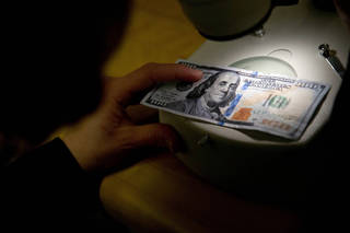 Marybeth Dellibovi, counterfeit specialist with the Secret Service, demonstrates inspecting a counterfeit $100 bill under a microscope in the counterfeit specimen vault room at the Secret Service headquarters in Washington. Photo by Andrew Harrer, Bloomberg News HARRER - BLOOMBERG NEWS