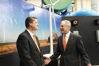 Oklahoma Gas and Electric President Peter Delaney, left, and Oklahoma State University President Burns Hargis speak Friday before a ceremony marking the completion of a 60-megawatt wind farm near Blackwell that will help supply electricity to the OSU campus in Stillwater. Photo By Paul Hellstern, The Oklahoman