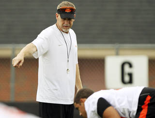 OKLAHOMA STATE UNIVERSITY / OSU COLLEGE FOOTBALL: New defensive coordinator Glenn Spencer (left) gives instructions to the defense during practice on August 2, 2013 in preparation for the fall season. Spencer is taking over defensive coordinator duties from departing coach Bill Young. Photo by KT KING, The Oklahoman