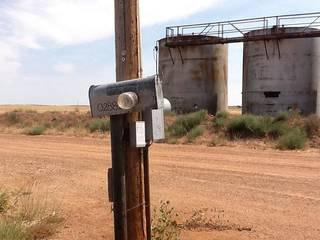 At this northwest Oklahoma oil site, truckers pump oil from tanks and leave paper receipts in the glass jar attached to a mailbox.