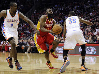 Houston Rockets' James Harden (13) heads for the basket between Oklahoma City Thunder's Serge Ibaka (9) and Kevin Durant (35) in the second half of an NBA basketball game, Wednesday, Feb. 20, 2013, in Houston. Harden scored 46 points in the Rockets' 122-119 win. (AP Photo/Pat Sullivan)