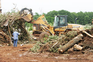 Oklahoma County District 2 workers sort tornado debris Wednesday at a burn pit near Harrah. PHOTOS BY STEVE GOOCH, THE OKLAHOMAN