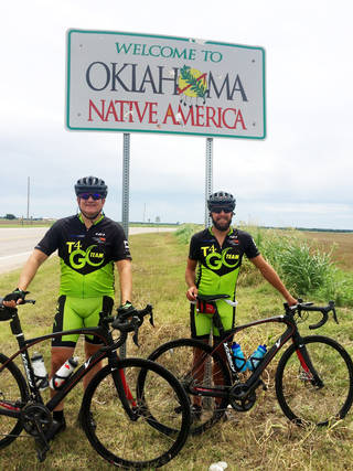 Ed Weaver, left, and Christian Toews are pictured at the Oklahoma/Kansas border during their coast-to-coast bike trip. They are with T4 Global, a Dallas-based ministry that wants to provide information for people in Third World countries who do not read. PHOTO PROVIDED PROVIDED