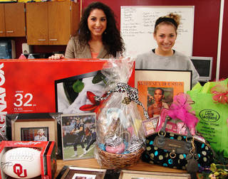 Kelsey Abraham, left, and Rylee Flowers stand with some of the items collected for the silent auction for Putnam City North High School's Heisman Week. A silent auction on Friday will be the first of many events Putnam City North High School students are staging to help Allie, 4, and Dylan, 14, who have life-threatening illnesses. Photo provided