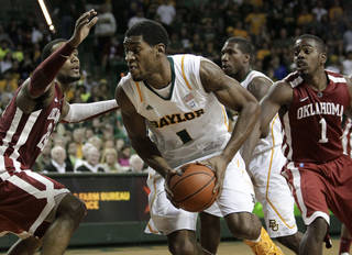 Baylor 's Perry Jones III (1) drives through Oklahoma defenders Romero Osby, left, and Sam Grooms (1) for a shot attempt in the second half of an NCAA college basketball game Saturday, Feb. 25, 2012, in Waco, Texas. Baylor defeated Oklahoma 70-60. (AP Photo/Tony Gutierrez) ORG XMIT: TXTG211