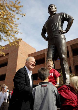 Along with his grandchildren Barry Switzer stands in front of a statue of himself after after it was unveiled before the college football game between the Texas A&M Aggies and the University of Oklahoma Sooners (OU) at Gaylord Family-Oklahoma Memorial Stadium on Saturday, Nov. 5, 2011, in Norman, Okla. Photo by Bryan Terry, The Oklahoman
