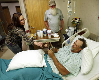 Kevin Troxell is shown one of the less revealing pictures of damage to his neighborhood by his sister-in law Cindy Hooper at Norman Regional Medical Center on Thursday, May 23, 2013 in Norman, Okla. His brother, Mark Troxell, is at center and is one of the relatives who was searching for Kevin and fearing the worst after Monday's tornado in Newcastele. Photo by Steve Sisney, The Oklahoman
