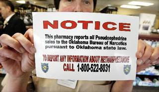 Dani Lynch, Thrifty Pharmacy owner, holds up a pseudoephedrine reporting sticker at Thrifty Pharmacy in Oklahoma City Tuesday, March 9, 2009. BY PAUL B. SOUTHERLAND