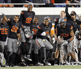 The OSU sideline reacts as Oklahoma State's James Thomas (22) returns an intercepted tipped pass during a college football game between the Oklahoma State University Cowboys (OSU) and the Kansas State University Wildcats (KSU) at Boone Pickens Stadium in Stillwater, Okla., Saturday, Nov. 5, 2011. Photo by Nate Billings, The Oklahoman