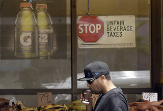 A man drinks out of a coffee cup as he walks under a sign opposed to taxes on sugary drinks posted in the window of Casa Thai Market in San Francisco. AP Photos Jeff Chiu