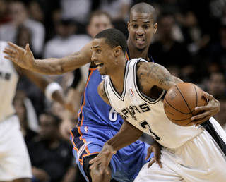 San Antonio's George Hill, front, drives around Oklahoma City's Eric Maynor during Monday's preseason game. AP PHOTO
