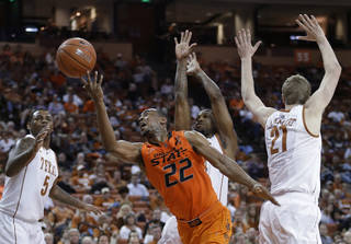 Oklahoma State's Markel Brown (22) shoots through Texas defenders Jaylen Bond (5), Connor Lammert (21) and Julien Lewis, center, during the second half of an NCAA college basketball game, Saturday, Feb. 9, 2013, in Austin, Texas. Oklahoma State won 72-59. (AP Photo/Eric Gay) ORG XMIT: TXEG106