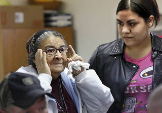 Guadalupe Fuentes, left, adjusts a new set of eyeglasses as she reads an eye chart to her daughter, Rosa Rodriguez, as Fuentes tries different pairs of glasses. Photos by Jim Beckel, The Oklahoman