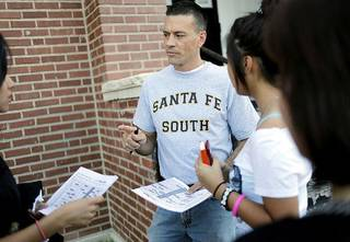 Superintendent Chris Brewster talks with students about their class schedules outside the school during the Back 2 School Bash at Santa Fe South Charter High School in Oklahoma City on Aug. 1. JOHN CLANTON - THE OKLAHOMAN
