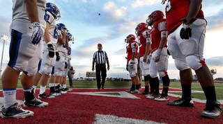 Team captains meet for the coin toss before a high school football game between the Carl Albert Titans and the Deer Creek Antlers. Photos by Steve Sisney, The Oklahoman