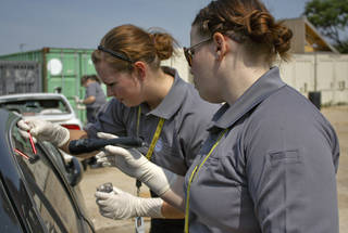 Audrey Mann and Melissa Lower dust for fingerprints on a car as part of their training as civilian investigation specialists. Photo by Adam Kemp, The Oklahoman