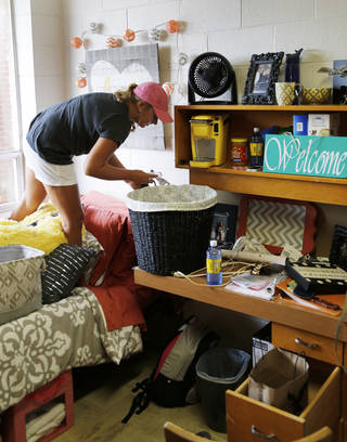 Incoming freshman Jessica Phillips, from Kingfisher, decorates her room in West Hall during move-in day at the University of Central Oklahoma in Edmond. PHOTO BY DOUG HOKE, THE OKLAHOMAN DOUG HOKE - THE OKLAHOMAN