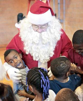 Joshua Powell, 7, left, and other children hug Santa on Friday at the City Rescue Mission. J.D. Simpson has been playing Santa at the shelter for nearly 30 years. Photo By David McDaniel, The Oklahoman