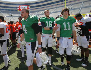OSU's J.W. Walsh, left, Deric Robertson, and Jake Hubenak walk towards fans after Oklahoma State's Orange Blitz football practice at Boone Pickens Stadium in Stillwater, Okla., Saturday, April 5, 2014.