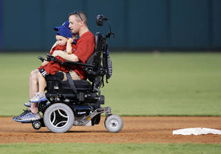 """MCKADE PEERY / MORGAN PEERY: Oklahoma City police officer Chad Peery and sons McKade, 6, background, and Morgan, 4, foreground, round the bases after the third inning as part of the """"Home Run for Life"""" promotion during the minor league baseball game between the Oklahoma City RedHawks and the Iowa Cubs at RedHawks Field at Bricktown in Oklahoma City, Saturday, Aug. 27, 2011. Peery was left paralyzed after being beaten while trying to break up a fight at bar earlier this year. Photo by Nate Billings, The Oklahoman ORG XMIT: KOD"""