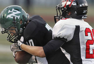 Norman North's Corbin Cleveland (20) catches a pass near the sideline defended by Addison Staggs (23) as the Norman North Timberwolves play the Westmoore Jaguars in high school football on Friday, September 16, 2011, in Norman, Okla. Photo by Steve Sisney, The Oklahoman
