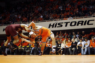 Oklahoma's 149-pound wrestler Kendric Maple and Oklahoma State's Josh Kendig grapple for position during a wrestling dual between Oklahoma State and Oklahoma at Gallagher Iba Arena in Stillwater on Feb. 9, 2014. Photo by KT King/For the Oklahoman