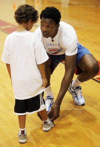 Hasheem Thabeet, center for the Oklahoma City Thunder, ties the shoes of Jay Kakani, 6 of Oklahoma City, at the Thunder basketball camp at Carl Albert High School in Midwest City on June 25, 2013. Photo by KT KING, The Oklahoman
