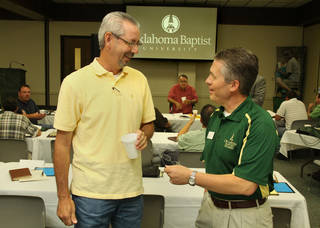 The Rev. John Cullison, bivocational pastor of First Baptist Church of Geronimo, visits with Dale Griffin, dean of spiritual life, during Oklahoma Baptist University's recent Pastors School. Photo Provided by Bill Pope, OBU