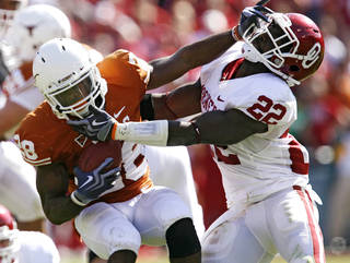 Oklahoma's Keenan Clayton (22) brings down Texas' Fozzy Whittaker (28) during last year's Red River Rivalry game. Photo by Chris Landsberger, The Oklahoman Archive.
