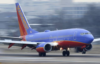 A Southwest Airlines jet plane lands at Love Field in Dallas. AP File Photo LM Otero - AP