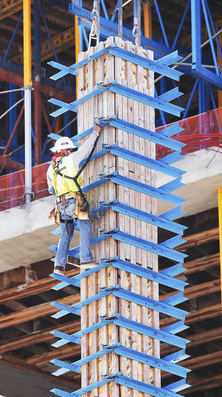 A worker climbs down from the top of this concrete column after attaching cables to the wooden forms so they can be removed by a crane after the cement set up. Photo by JIM BECKEL, THE OKLAHOMAN ARCHIVES
