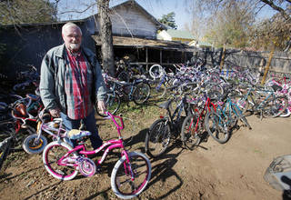 John Ballard poses with some of the bikes he repairs to give to children. Photo By Steve Gooch, The Oklahoman