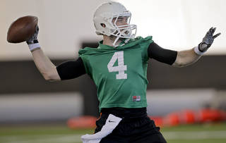 Oklahoma State quarterback J.W. Walsh throws a pass during the first day of spring football practice at Oklahoma State University in Stillwater, Okla., on Monday, March 10, 2014. Photo by Chris Landsberger, The Oklahoman
