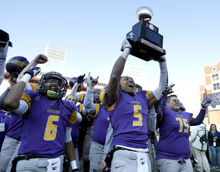 Anadarko's RJ Sink holds up the Championship trophy following the Class 4A State Football Championship game between Anadarko and Poteau at Boone Pickens Stadium in Stillwater, Okla. Photo by Sarah Phipps, The Oklahoman