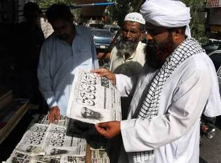 "People read newspapers at a news stand carry headlines ""Osama bin Laden killed."" in Hyderabad, Pakistan on Monday, May 2, 2011. Osama bin Laden, the mastermind behind the Sept. 11, 2001, terror attacks that killed thousands of people, was slain in his hideout in Pakistan early Monday in a firefight with U.S. forces, ending a manhunt that spanned a frustrating decade. (AP Photo/Pervez Masih)"