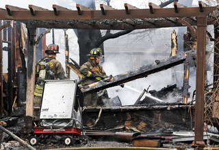 Oklahoma City firefighters put out hot spots Wednesday at a house fire. Photo by Nate Billings, The Oklahoman