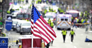 A flag flies over the finish line as medical workers aid injured people following an explosion at the finish line of the 2013 Boston Marathon in Boston, Monday, April 15, 2013. Two explosions shattered the euphoria at the finish line, sending authorities out on the course to carry off the injured while the stragglers were rerouted away from the smoking site of the blasts. (AP Photo/Charles Krupa) ORG XMIT: MACK124