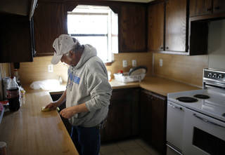 David Colon, a veteran who was facing homelessness, cleans the kitchen of the home he moved into with the help of Goodwill Industries. Photo by Sarah Phipps, The Oklahoman SARAH PHIPPS -